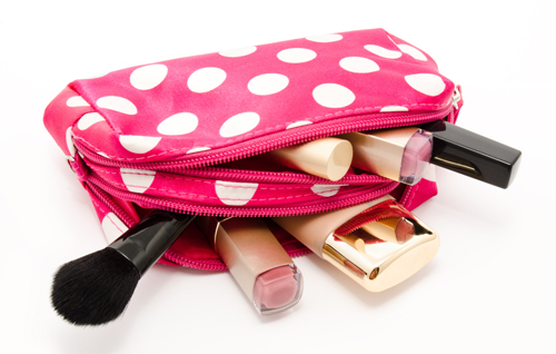 Pink make up bag with cosmetics isolated on a white background
